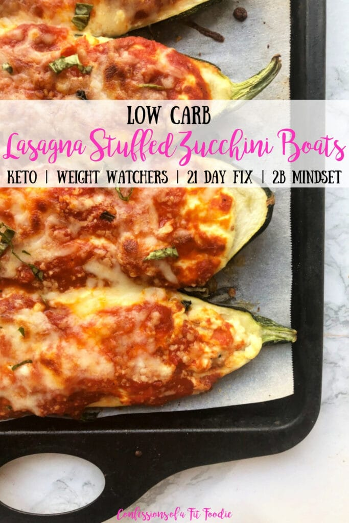 Baking sheet with Lasagna Stuffed Zucchini Boats on a marble backdrop. Boats have been broiled and the cheese is bubbly and crispy. Has the text overlay- Low carb Lasagna Stuffed Zucchini Boats - Keto | Weight Watchers | 21 Day Fix | 2B Mindset - Confessions of a Fit Foodie