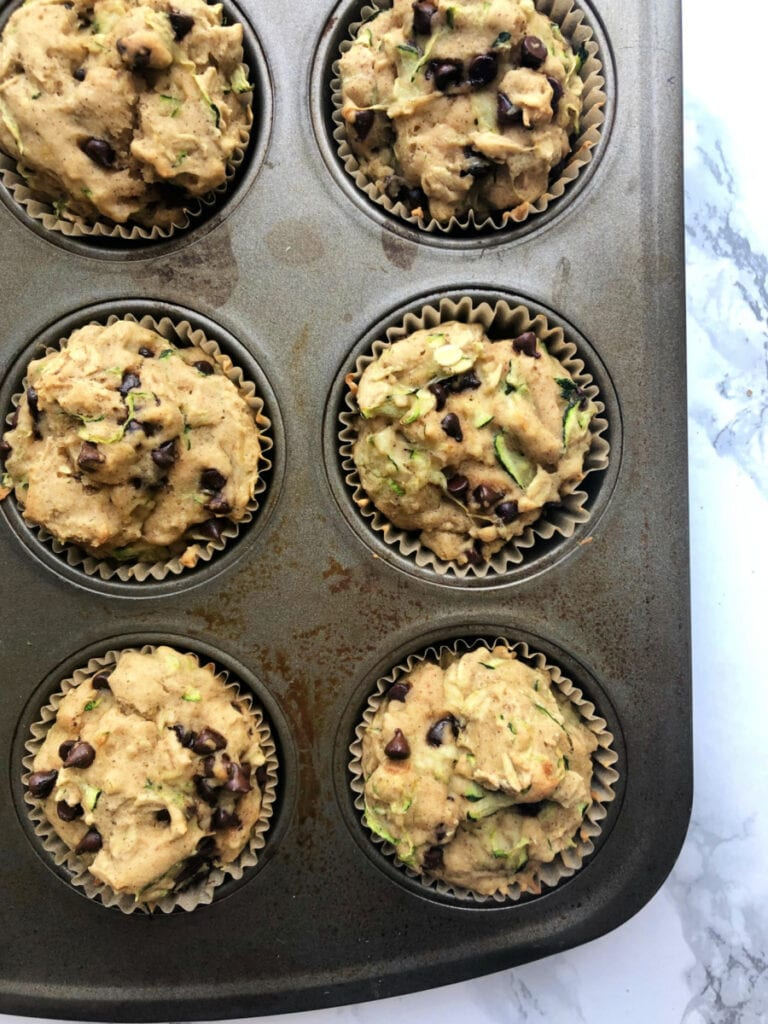 Close up photo of a partial muffin pan filled with fresh out of the oven Gluten Free Chocolate Chip Zucchini Muffins