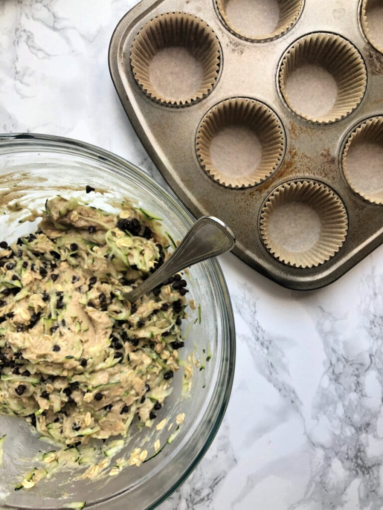 Overhead photo of Gluten free chocolate chip zucchini muffin batter in a glass bowl next to a muffin tin lined with parchment muffin liners.