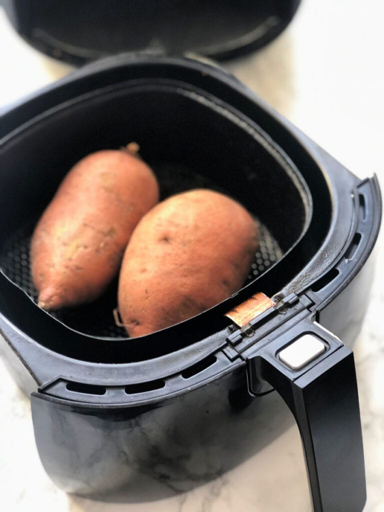 Two sweet potatoes in an air fryer