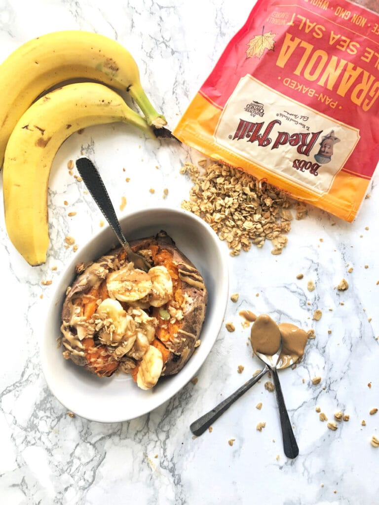 A bowl of sweet potato stuffed with banana and peanut butter on a marble counter. Bananas and a bag of Bob's Red Mill Maple Sea Salt granola are sitting on the counter nearby