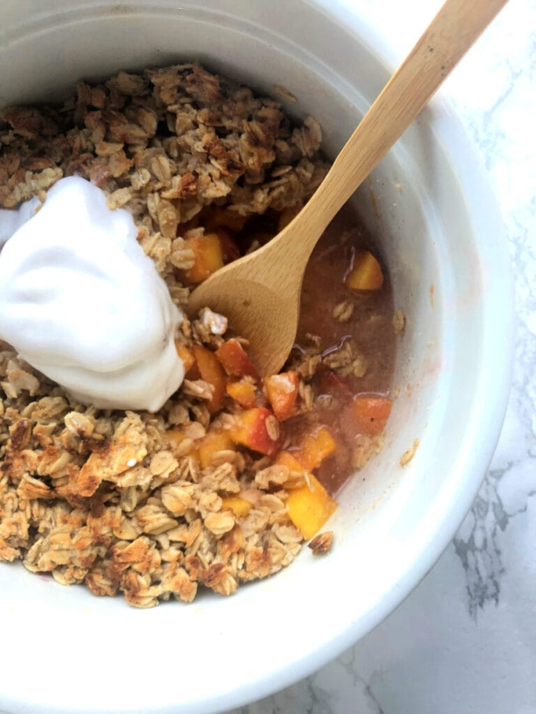 A big Instant Pot safe casserole dish with Instant Pot peach crisp topped with oats, almond flour, and so delicious coconut cream
