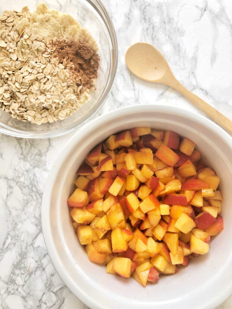 Diced peaches in a large casserole bowl sitting next to a bowl of oats, almond flour and cinnamon - this will be the topping for a Healthy Peach Crisp