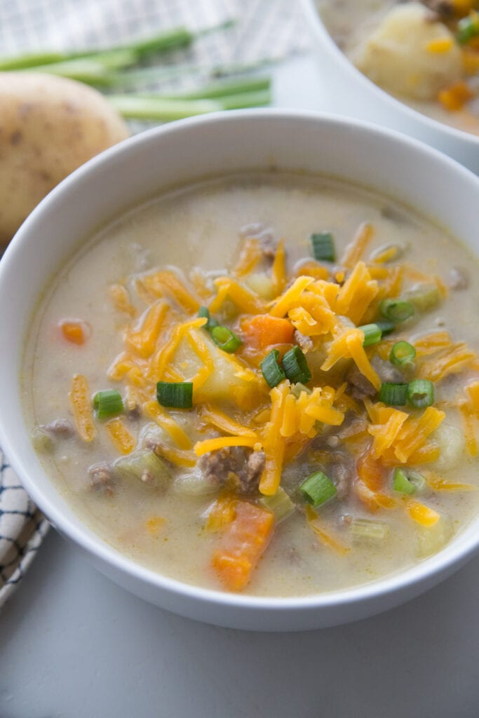 A bowl full of creamy Cheeseburger Soup topped with cheddar cheese and green onions sitting on a white table with a second bowl in the background