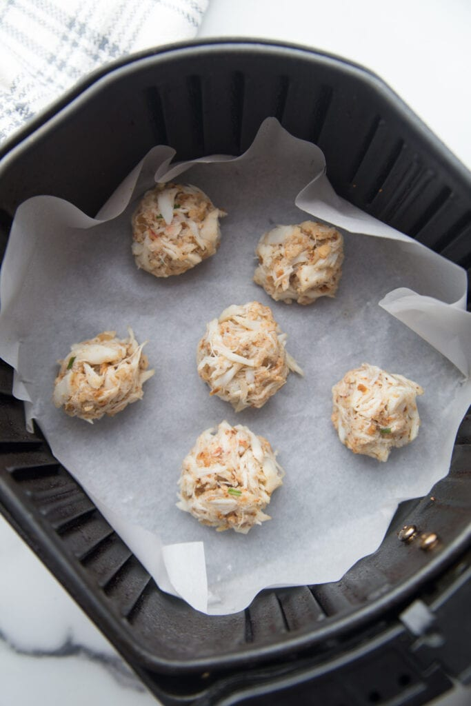 An air fryer basket lined with parchment paper with mini crab cakes