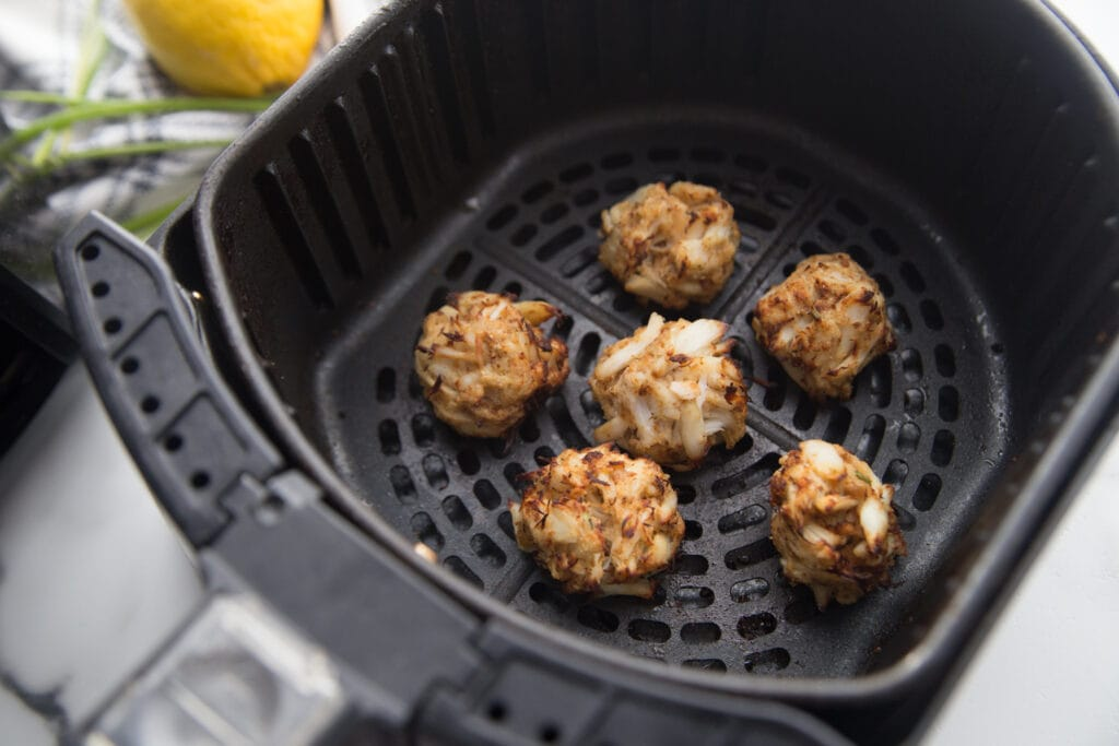 Air fryer basket with mini crab cakes that are gluten free