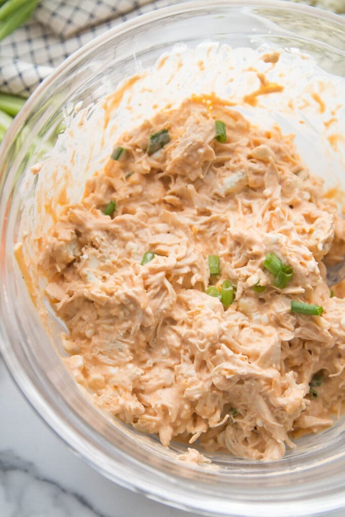 Overhead view of buffalo dip mixed with shredded chicken and topped with sliced green ontions