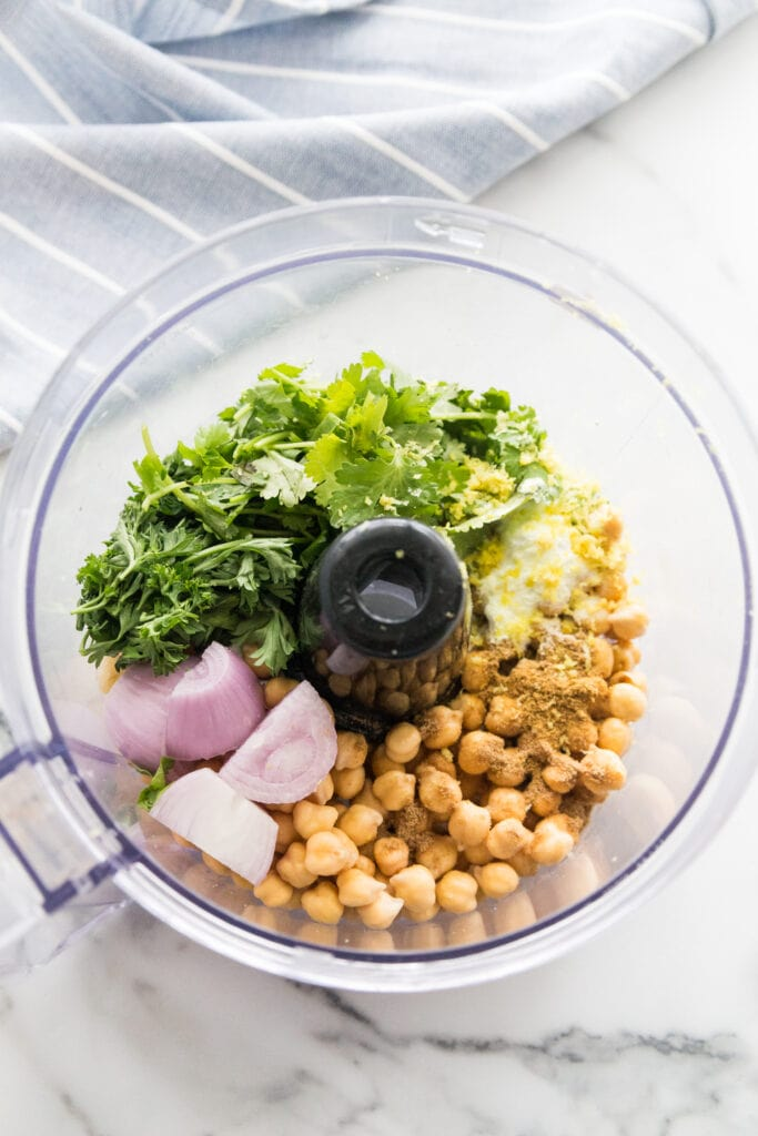 Overhead view of a food processor with separated ingredients to make falafel - chickpeas, spices, lemon zest, fresh cilantro, fresh parsley, shallots. The food processor is on a white marble background with a blue and white striped towel to the upper left corner.