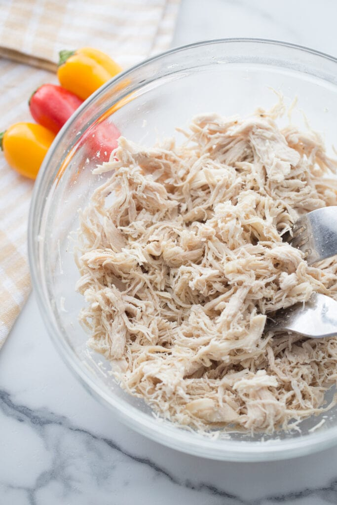 Shredded chicken in a glass bowl with two forks, mini bell peppers are in the background