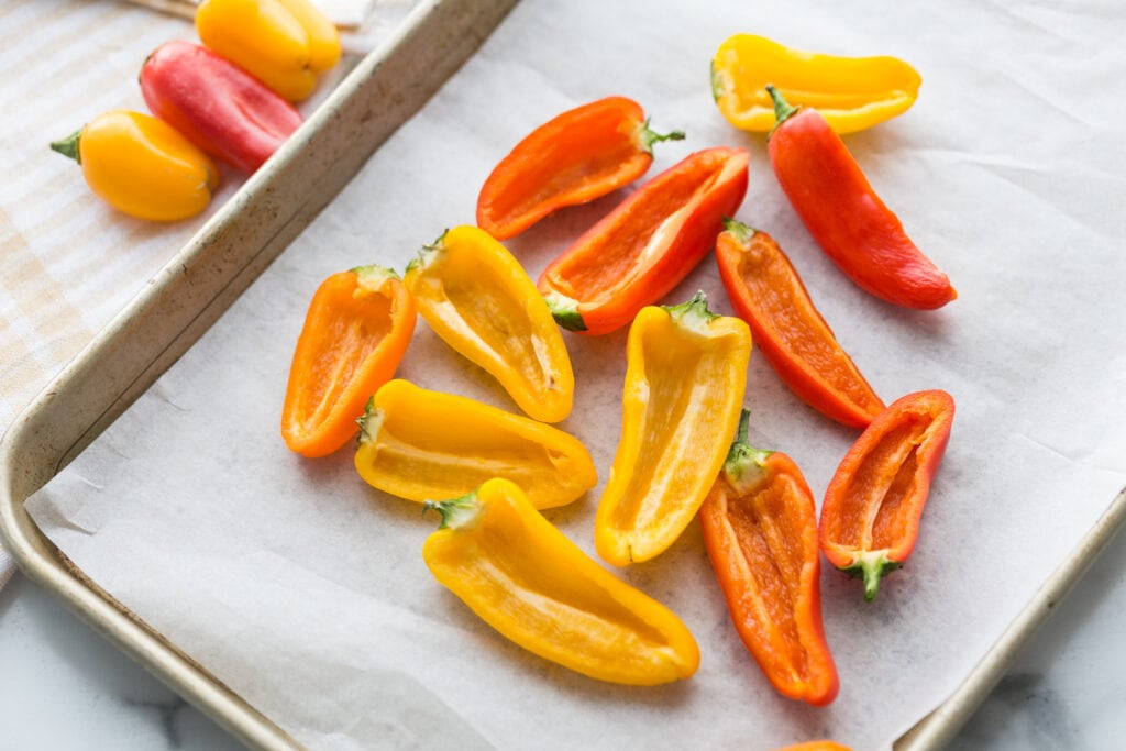 Red, Orange, and Yellow halved, seeded mini bell peppers on a parchment lined sheet pan