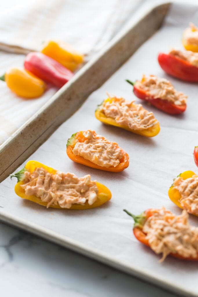 Close up side angle of a Sheet pan lined with parchment paper with rows of orange and yellow mini Healthy Buffalo Chicken Dip Stuffed Peppers