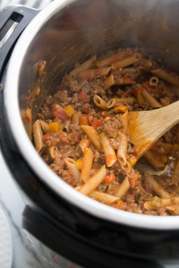 A wooden spoon mixing Instant Pot Enchilada Pasta for the 21 Day Fix
