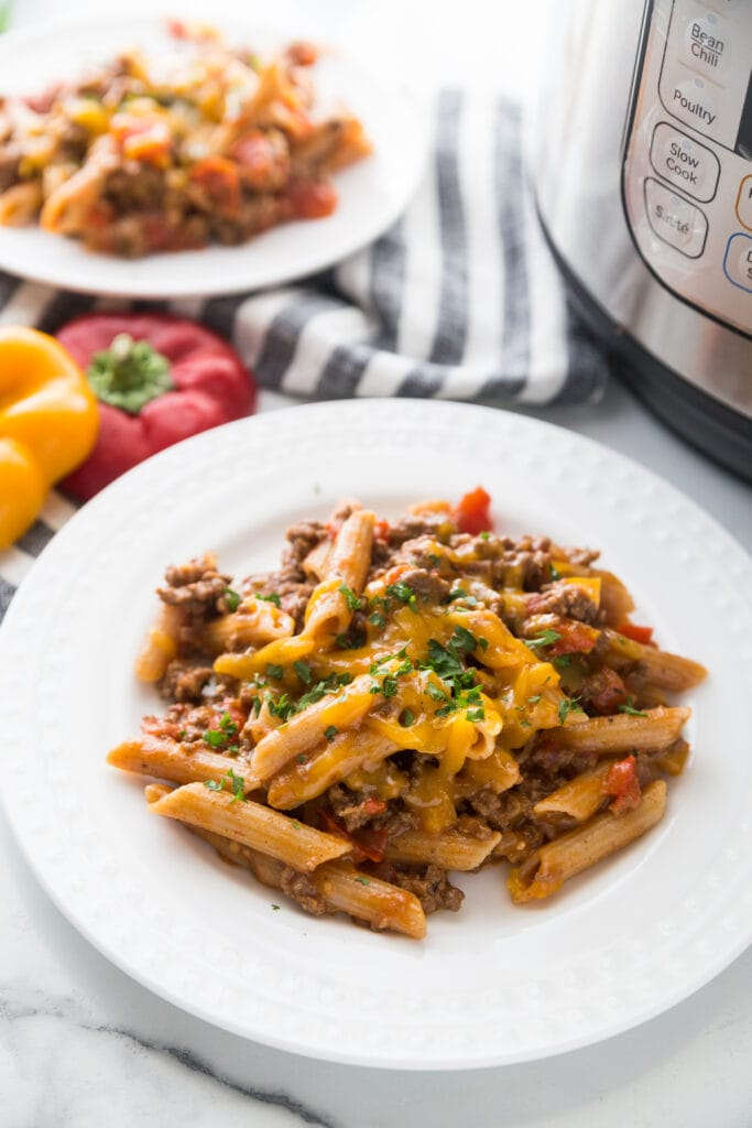 A plate of cheesy beef Instant Pot enchilada pasta with lots of veggies sitting next to an Instant Pot