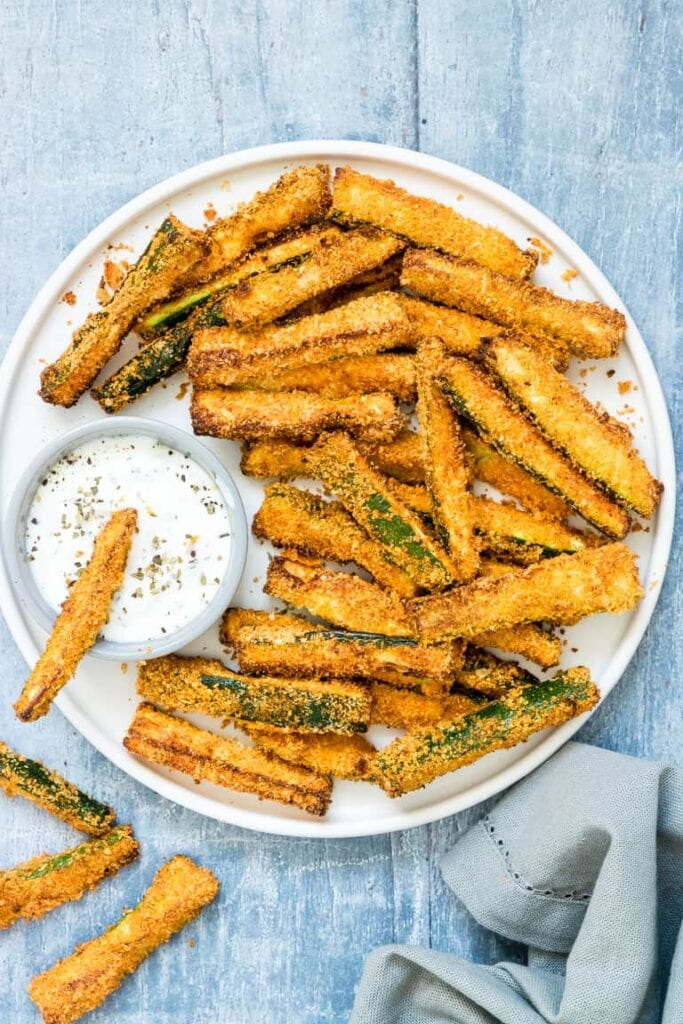 Overhead photo of Crispy Air Fryer Zucchini Fries on a white plate with dipping sauce on the side
