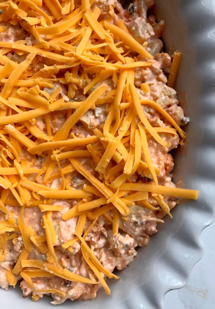 Close up photo of buffalo cauliflower dip topped with shredded cheddar, ready for the oven