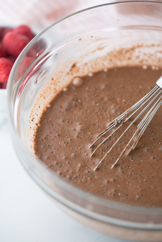 Close up photo of glass bowl full of chocolate chia pudding and a whisk, before being chilled