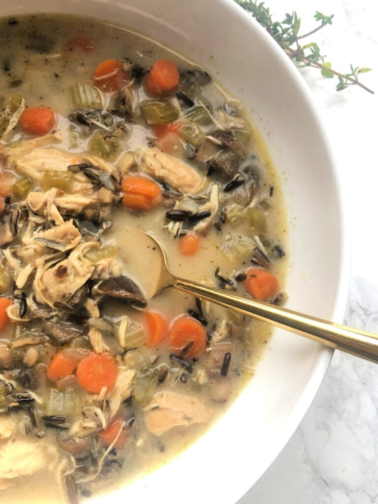 Overhead photo of a white bowl full of Instant Pot Chicken and Wild Rice Soup with a gold spoon on the side and a white marble background. In the soup there are diced carrots, celery and mushrooms, shredded chicken, wild rice, and a creamy broth.