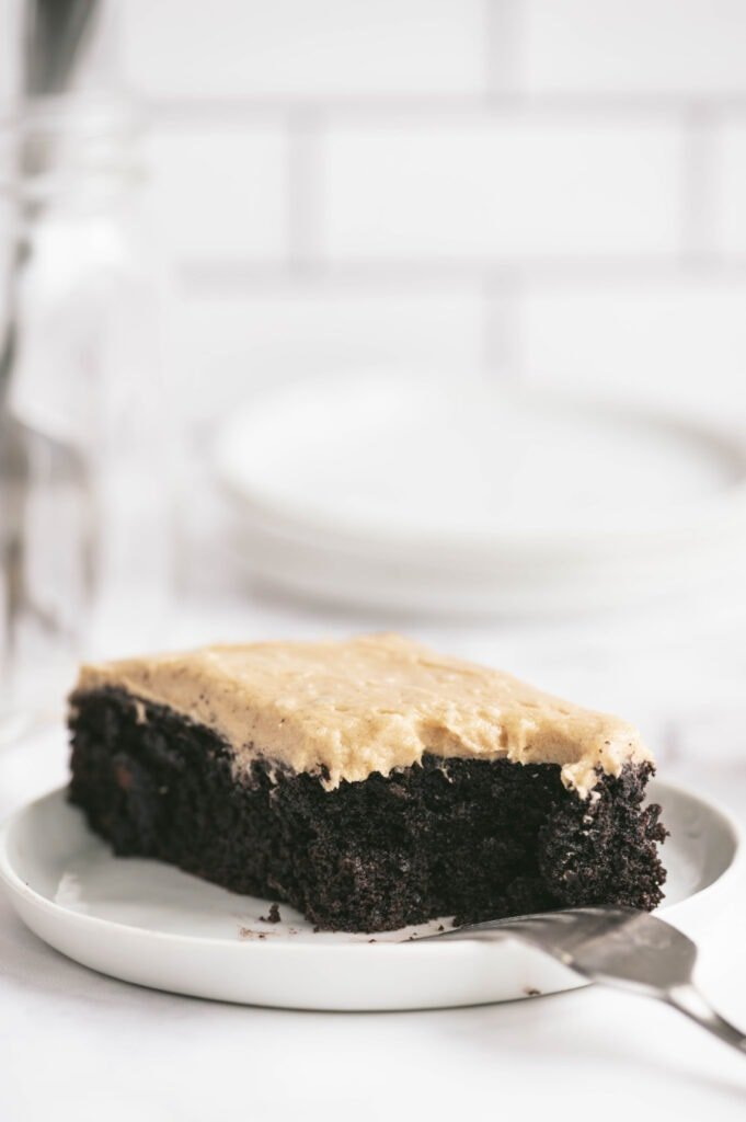 Close up side view of a rectangular piece of Chocolate cake topped with peanut butter frosting on a round white plate with a fork poised upside down on the rim.