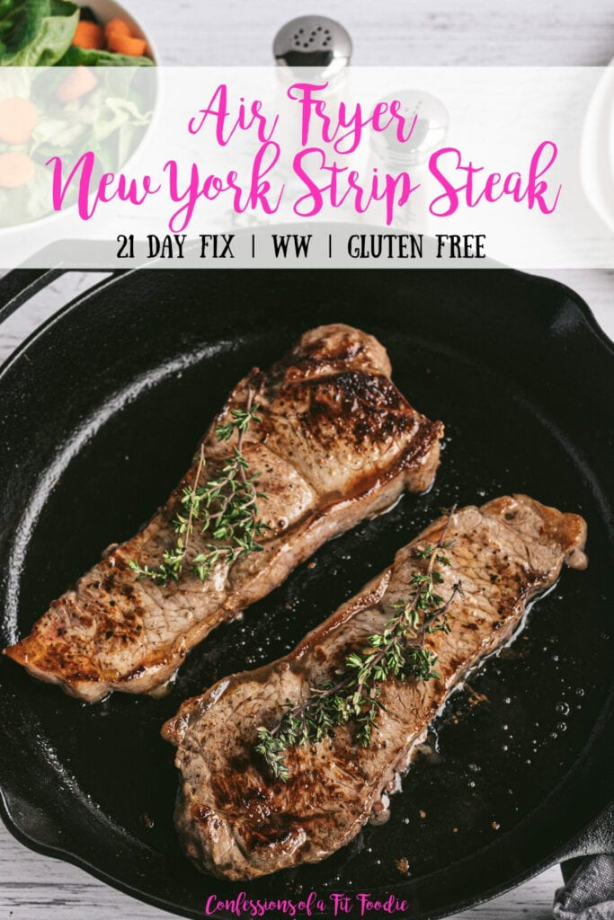 Overhead photo of Two New York Strip Steaks grilled in a Cast Iron Skillet with salt and pepper shakers and a salad in the background. With the text overlay- Air Fryer New York Strip Steak | 21 Day Fix | WW | Gluten Free | Confessions of a Fit Foodie