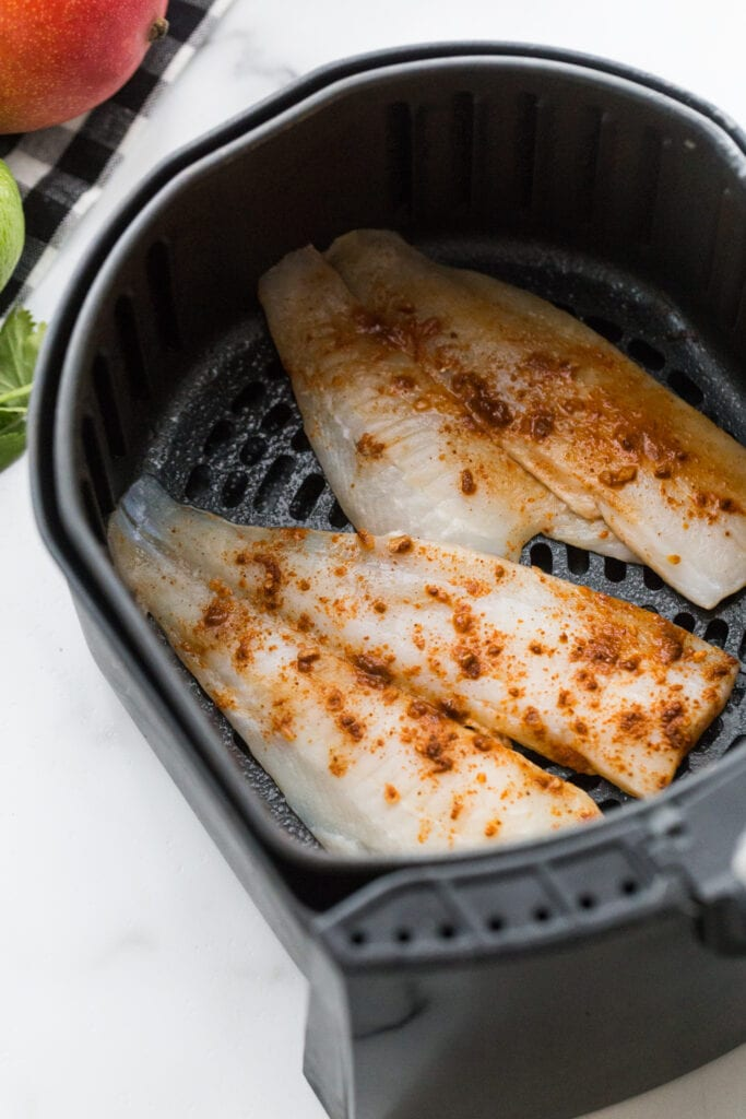 Seasoned white fish filets in an air fryer basket, ready for fish tacos