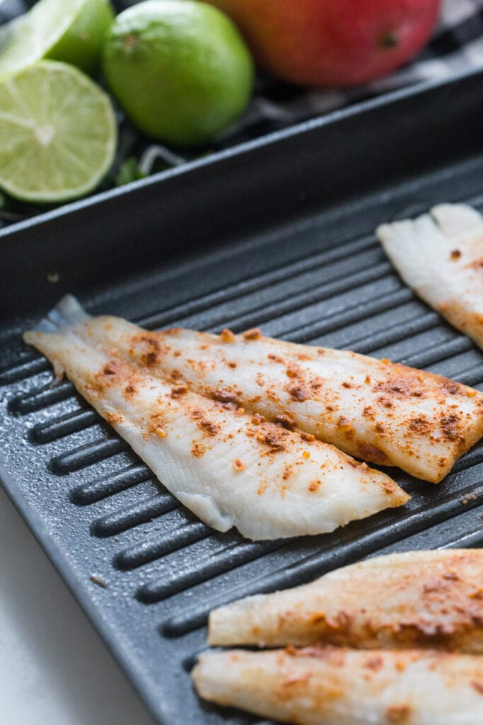 Seasoned White fish filets on a grill pan, ready to be cooked for fish tacos. Limes and mangoes are in the background.