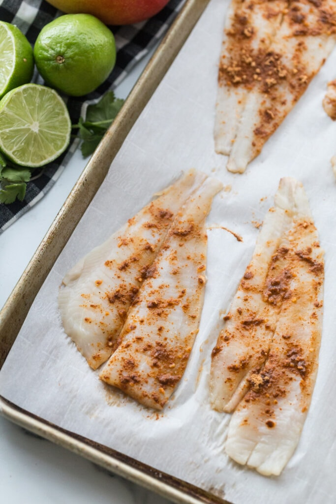 Seasoned white fish filets, on a parchment lined sheet pan, ready for the oven, with fresh limes on the side of the pan.