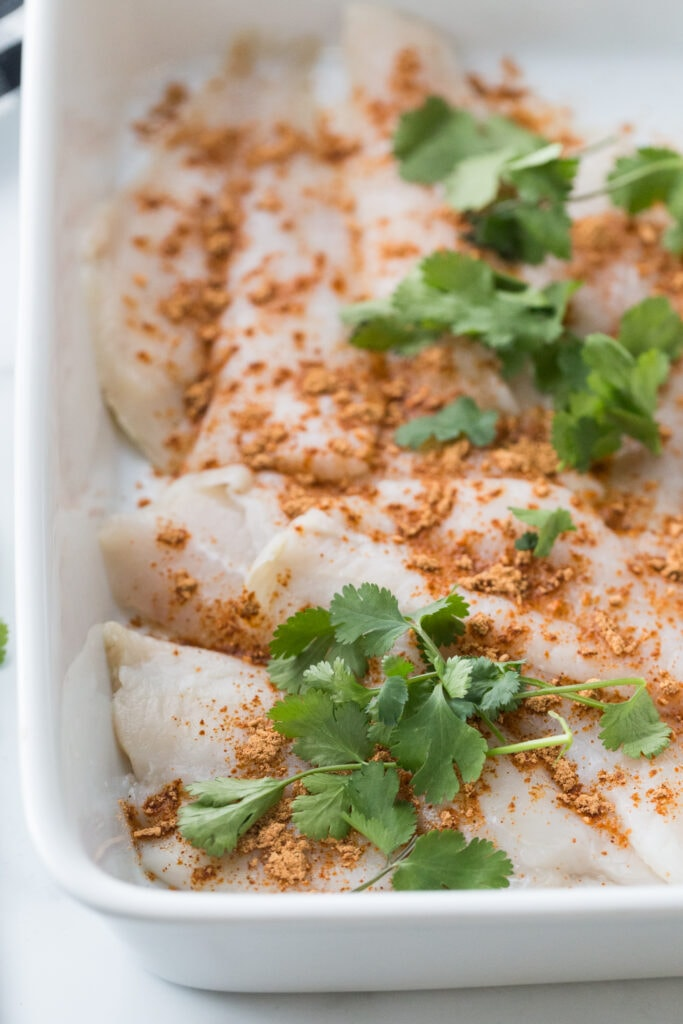 White fish in a white baking dish, topped with spices and cilantro ready to be cooked for fish tacos.