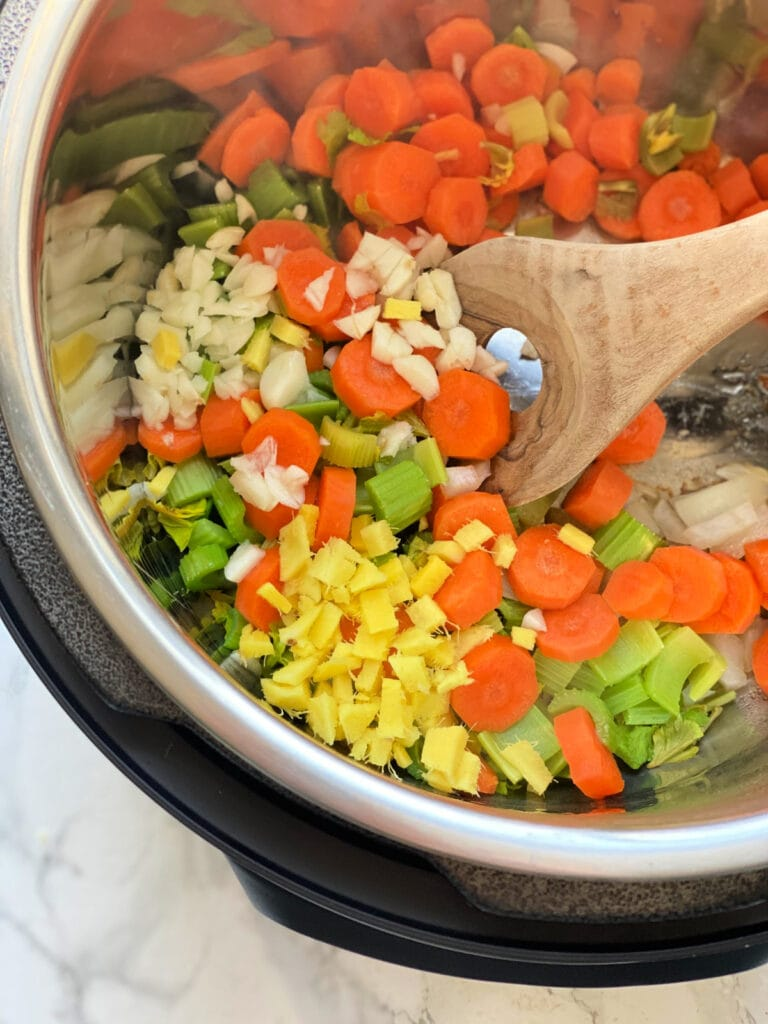 Overhead photo of sliced carrots, celery, onions, garlic, and fresh ginger being sauteed in an Instant Pot, the beginning of Chicken Noodle Soup.