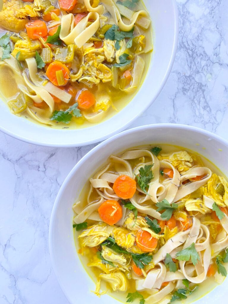 Overhead photo of two hearty bowls of Chicken Noodle Soup filled with sliced carrots, cilantro, egg noodles, and chicken with a beautiful yellow broth colored by Turmeric,