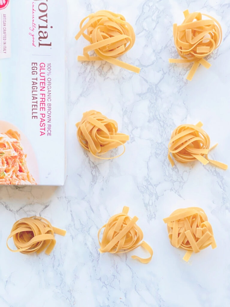 "Overhead photo of Gluten Free egg noodle ""nests"" on a white marble background. A box of Jovial brand noodles is on its side, half out of frame."