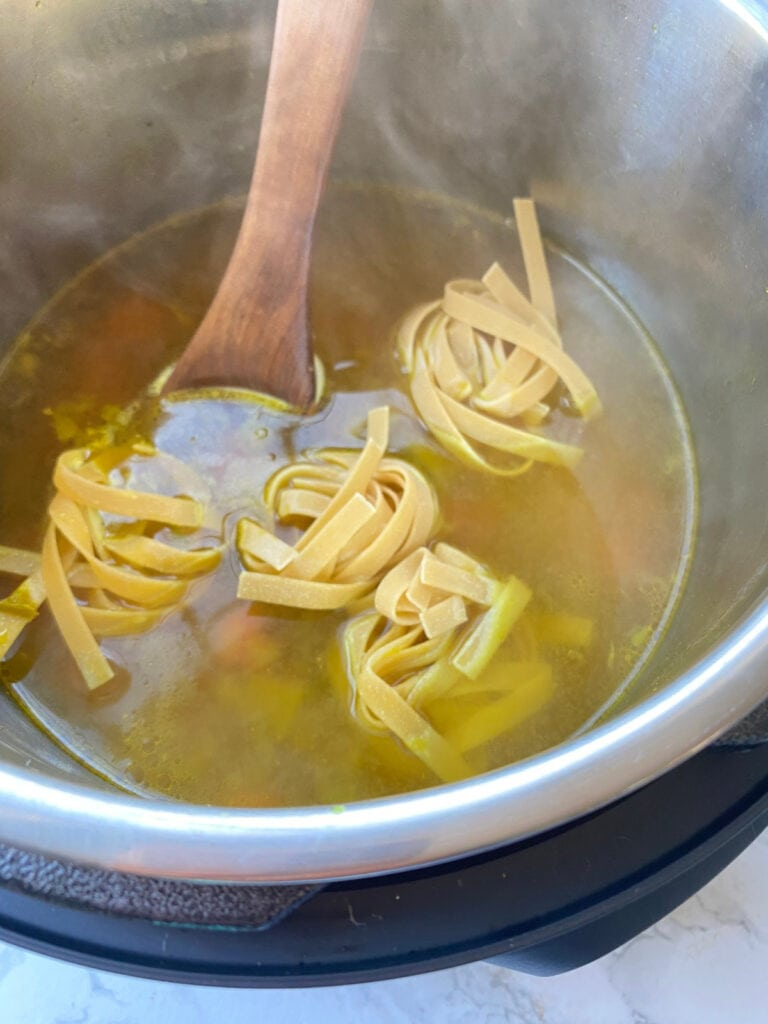Egg noodles being cooked in soup broth in the Instant Pot for chicken noodle soup.
