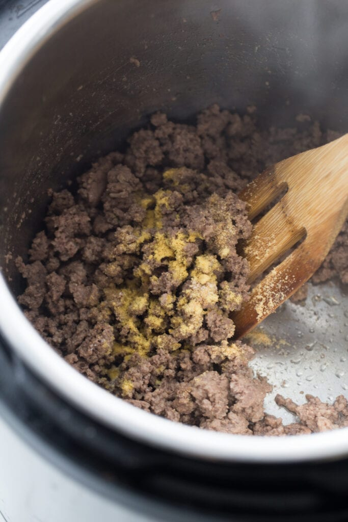 Overhead view of an Instant Pot full of browned ground beef, topped with spices. There is a slotted wooden spoon stirring the meat.