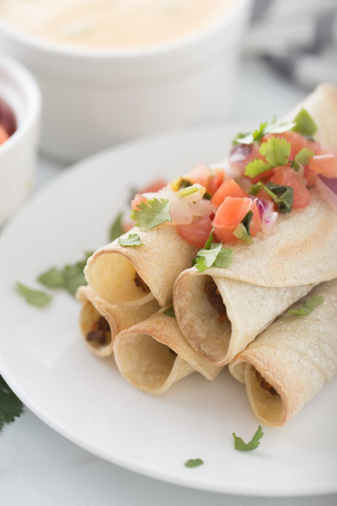 Close up photo of a plate stacked with beef taquitos.topped with homemade salsa. In the background, out of focus, are ramekins filled with salsa and cheese sauce.