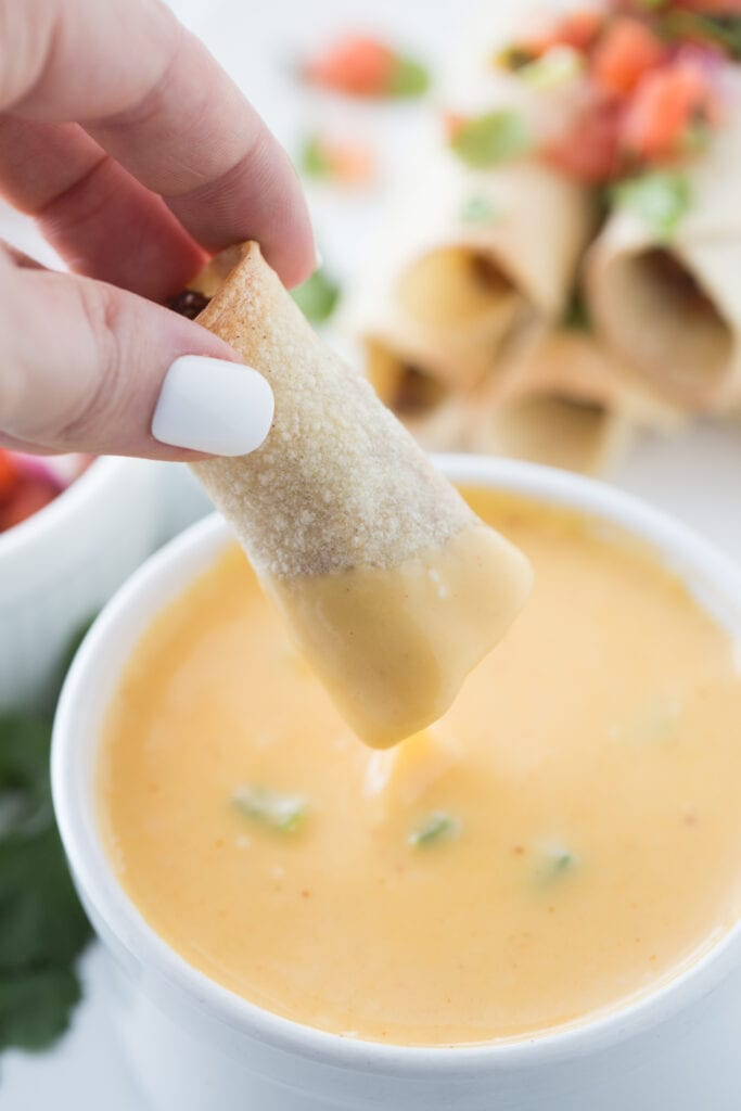 Woman's hand with white nail polish is holding a beef taquito and dipping it into a bowl of cheese sauce. In the background, out of focus, is a stack of taquitos topped with homemade salsa.