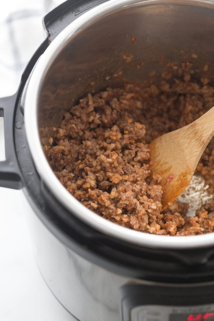 High angle photo of an instant pot and wooden spoon stirring beef taquito filling.