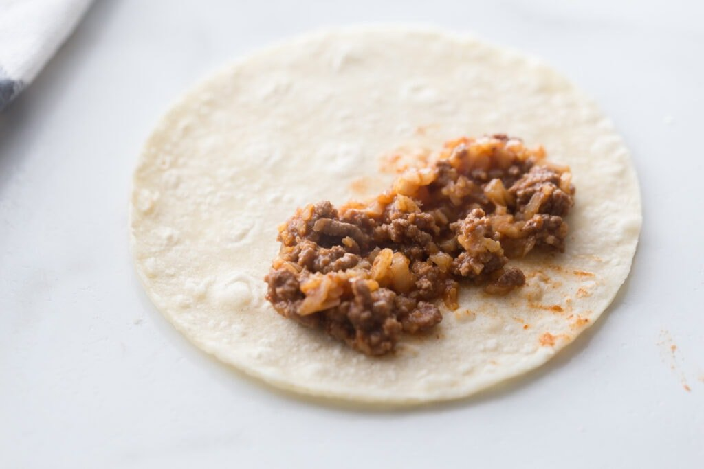 A corn tortilla filled with cauliflower beef taquito filling on a white counter top
