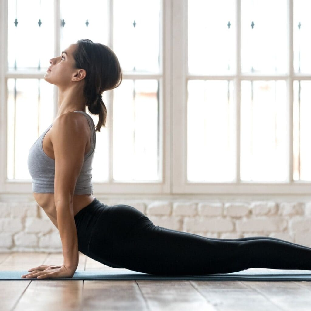 A side view of a dark haired woman with a low bun in upward dog yoga pose on a dark yoga mat which is on a wooden floor. She is wearing black pants and a gray cropped workout tank. There is a whole wall of windows behind her with light shining though.