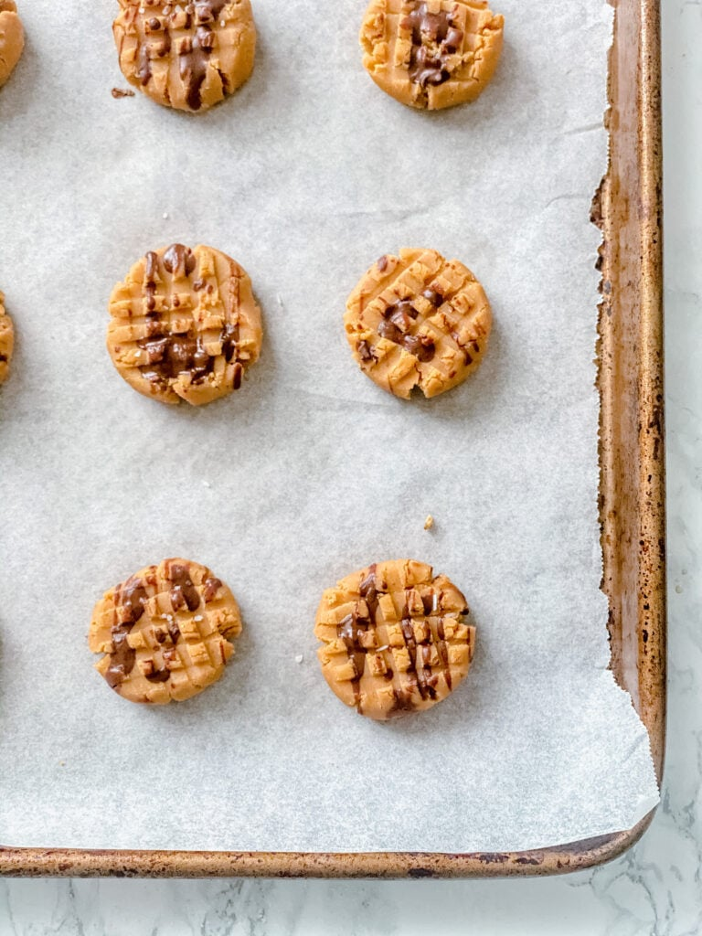 Overhead photo of No Bake Peanut Butter Cookies drizzled with chocolate on a parchment lined cookie sheet on a white marble background.