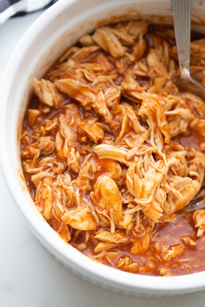 Overhead photo of pulled BBQ chicken in a white casserole dish, fresh from the Instant Pot with a spoon, ready to serve.