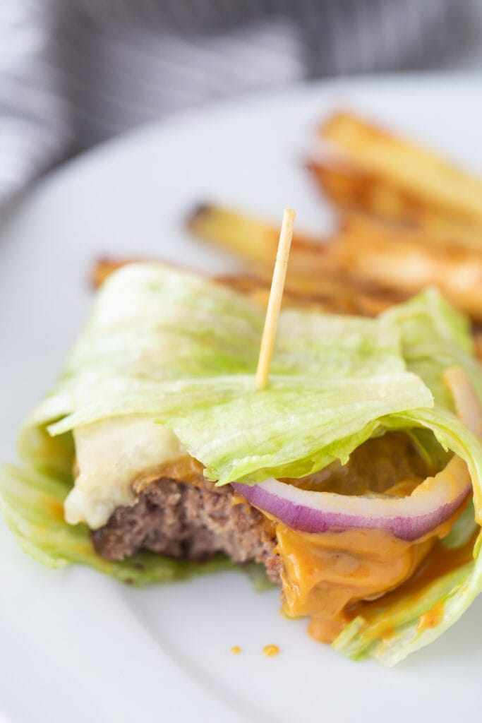 A toothpick is holding together a lettuce wrapped burger with delicious toppings and burger sauce, with homemade french fries in the background.