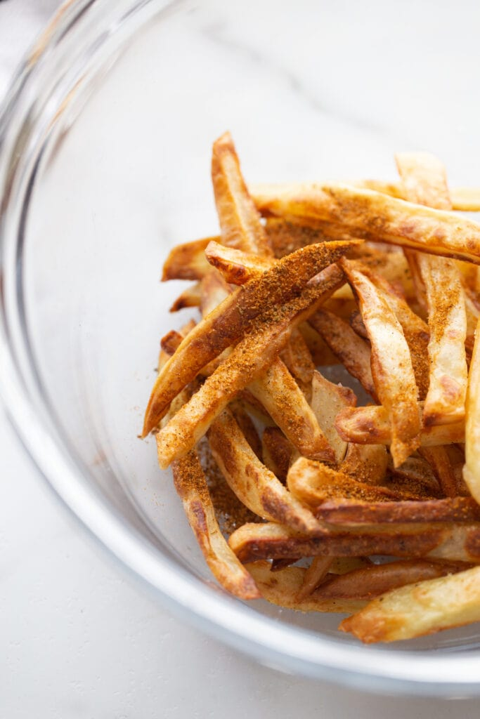Close up photo of homemade seasoned crab fries in a glass bowl on a white surface.
