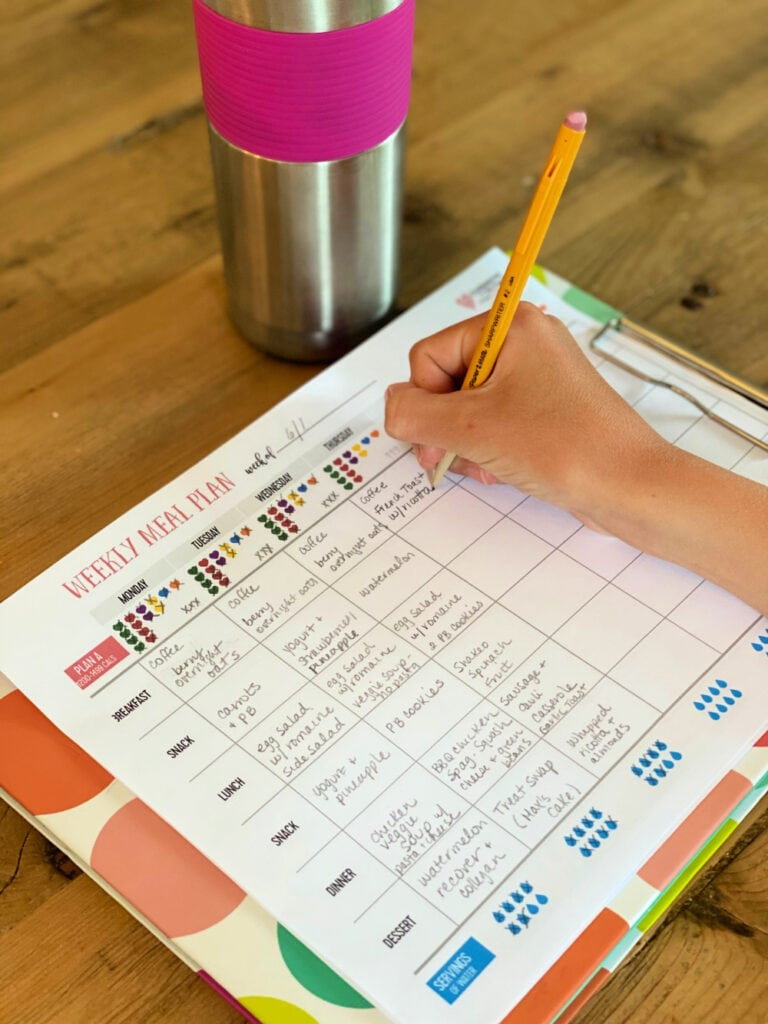 A hand holding a pencil and writing in a 21 Day Fix meal planner tracking sheet on a colorful clip board on a wooden table. There is a metal water bottle with a pink grip at the top of the photo.
