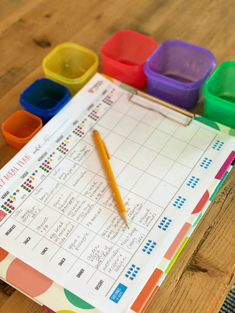 Color coded paper meal tracking sheet for the 21 Day Fix on a colorful clip board with a pencil on top. Next to the clip board are the colored containers for tracking food on the 21 Day Fix.