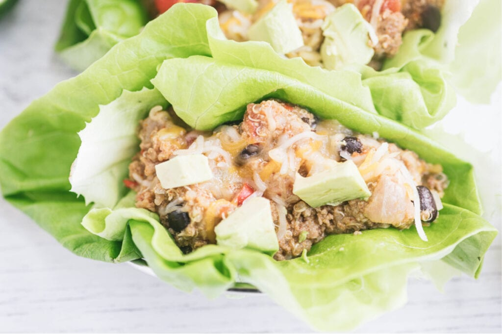 Close up photo of crock pot taco casserole in a lettuce wrap and topped with avocado.