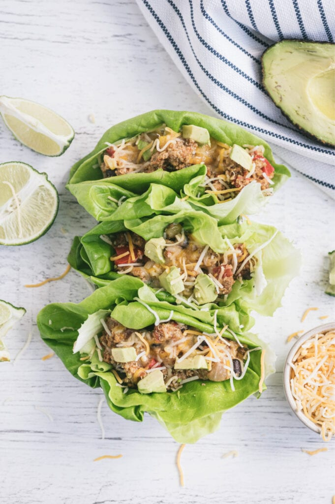 Overhead photo with lettuce wraps filled with Mexican crock pot taco casserole on a white surface. Surrounding the wraps are a white and blue striped towel, half an avocado, sliced limes, and a ramekin full of shredded cheese.