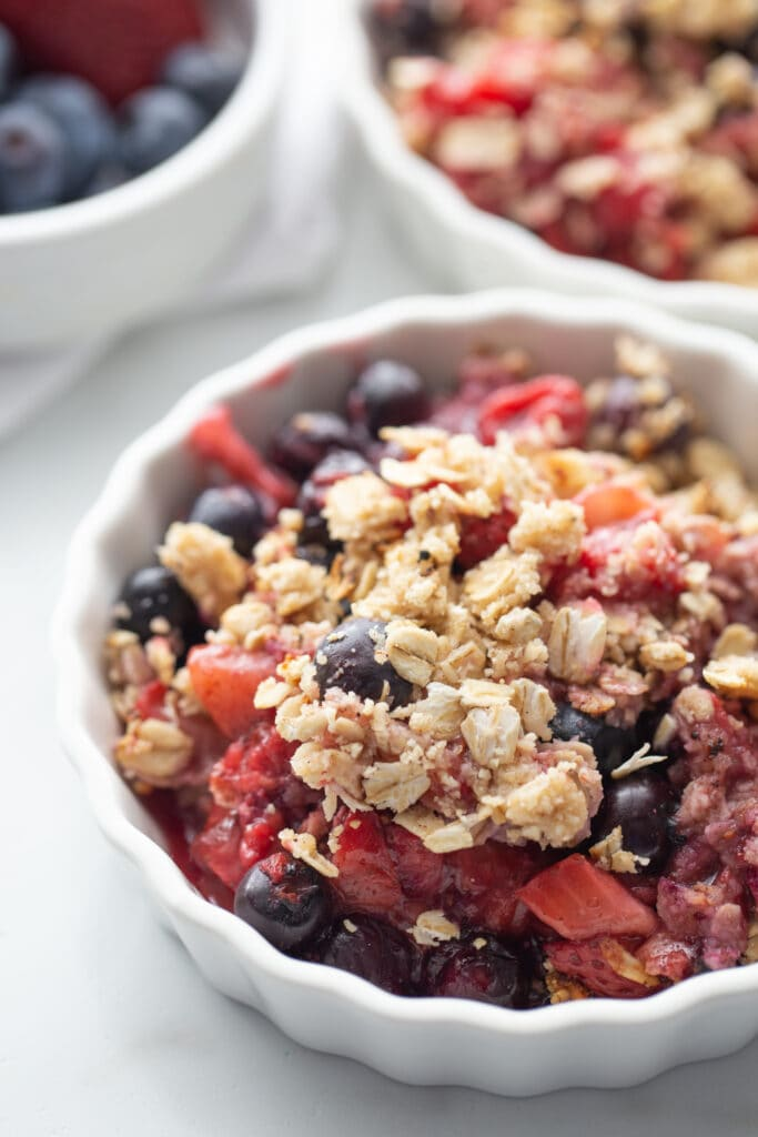 Mixed berry crisp with gluten free oat topping in shallow ramekin. In the background, out of focus, are two more white ramekins of blueberry crisp with strawberries and raspberries..