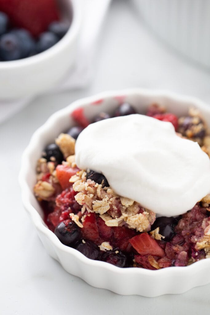 Close up photo of an individual mixed berry crisp topped with homemade coconut cream.