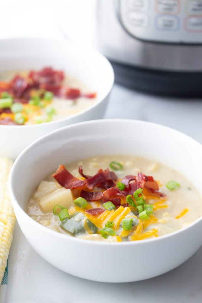 Two bowls of corn chowder topped with bacon, cheese, and green onions sit on a white table in front of an instant pot brand pressure cooker