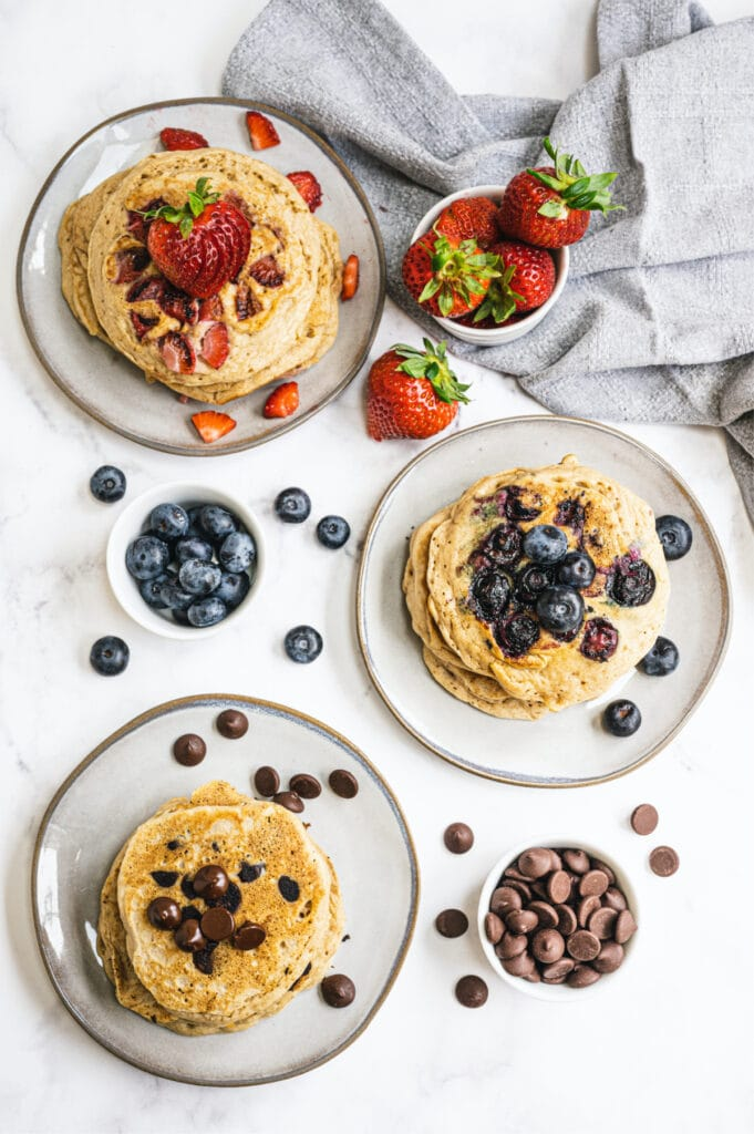 Overhead photo of three plates with short stacks of pancakes, each with a different topping/mix in. Strawberries, blueberries, and chocolate chips are all around the plates and on the white counter top.