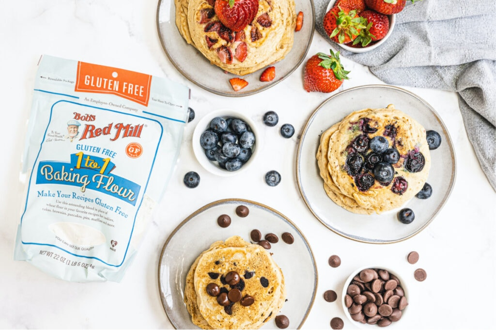 Overhead photo showing plates of pancakes topped with fruit or chocolate chips. A bag of Bob's Red Mill Gluten Free 1 to 1 Baking Flour is off to the side showing the wonderful base for cooking the Gluten Free pancakes.